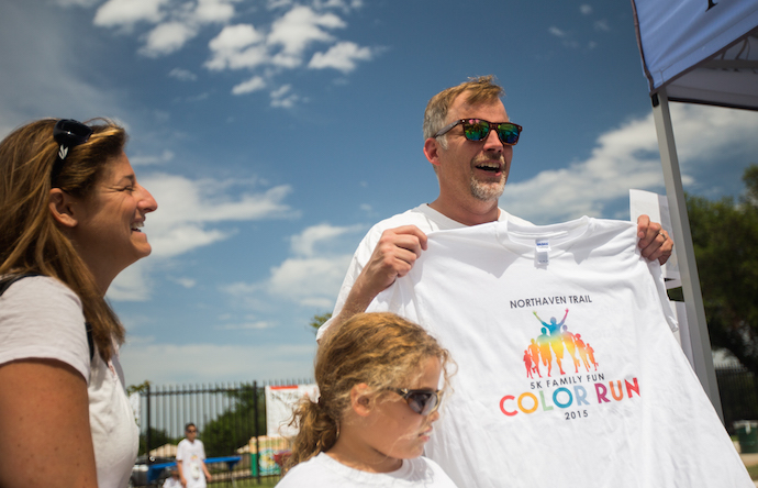 Teddy Howard picks up a t- shirt with his wife Debra and daughter Reese. Photo by James Coreas