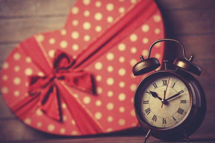 Retro clock and gift in heart shape on the background.