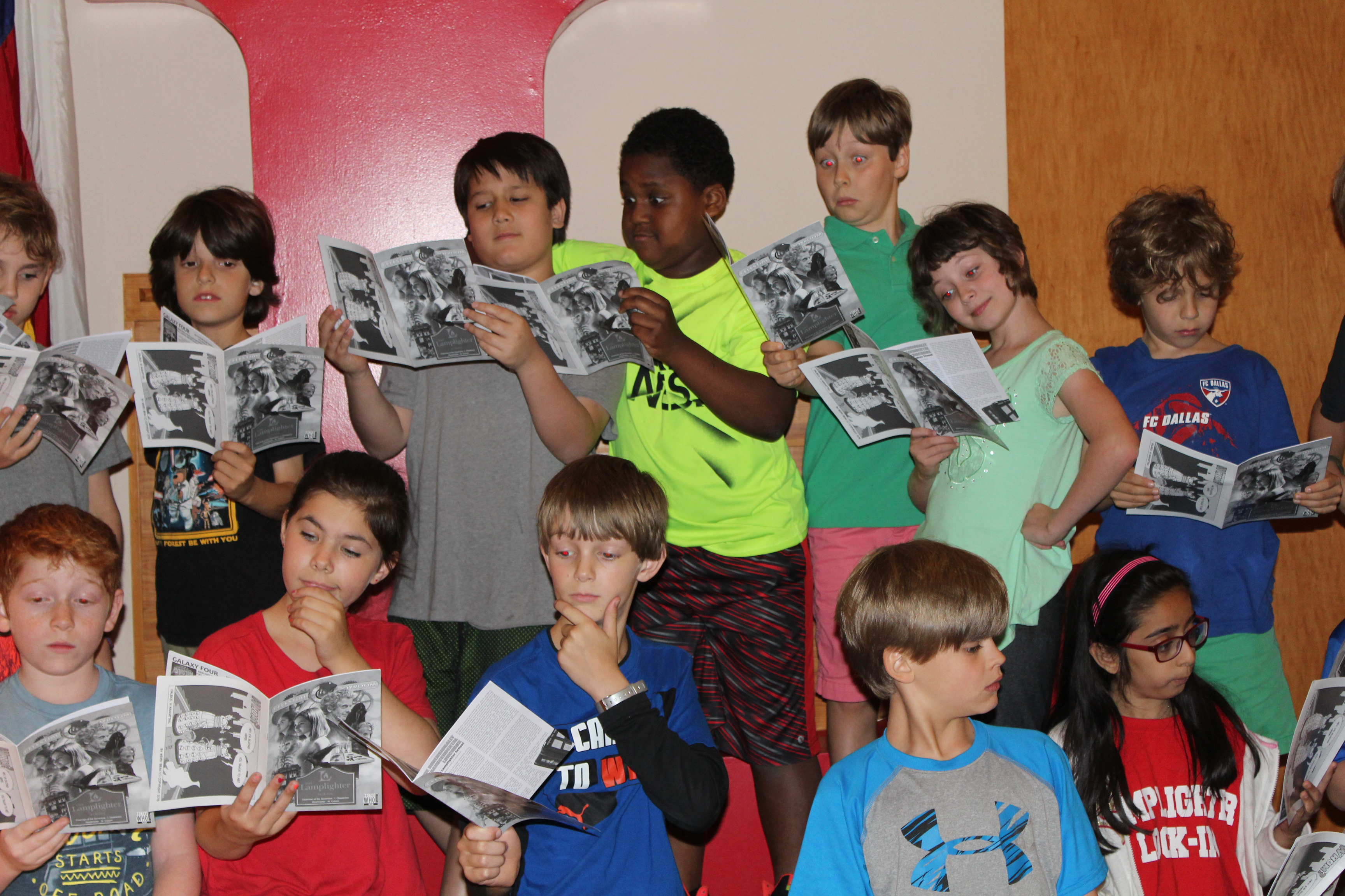 """Members of the """"Who Is Doctor Who"""" fan club at the Lamplighter School check out their cover story in Celestial Times magazine, official publication of the Doctor Who Appreciation Society. (Photo from Lamplighter School)"""